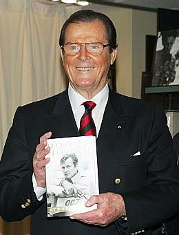 Roger Moore holding his autobiography