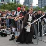A fan dressed as Obi-Wan from Star Wars waits patiently with the rest of the crowd to get in