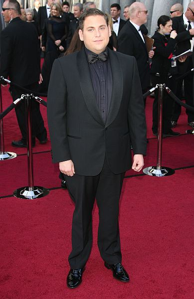 Jonah Hill definitely pulled out all the stops when it came to his look for this year's Oscars. He went with the standard black satin collar tux but instead of the usual white shirt, he paired it with a dark shirt and then a black satin bow tie. His Ermenegildo Zegna ensemble was a definite […]