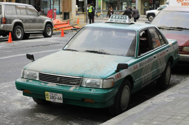 A parked taxi covered with debris. Photo by Sue Holland.