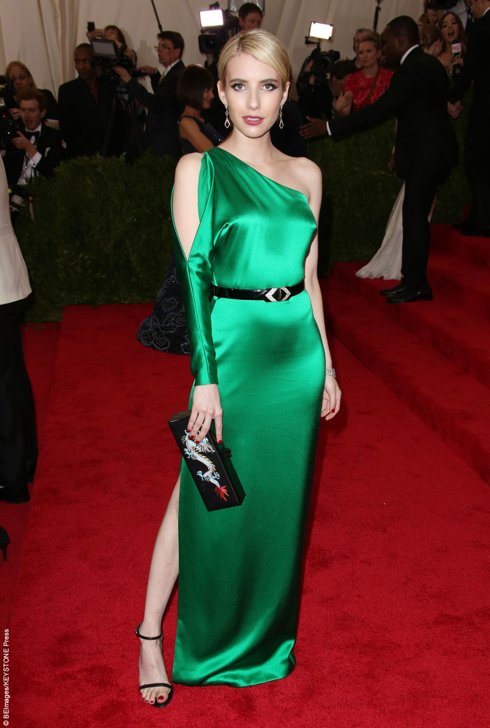Emma Roberts walked the red carpet in a glamorous emerald silk Ralph Lauren gown. The old Hollywood look contrasted the red carpet and hugged her slim frame perfectly. To match theevent'sChina: Through the Looking Glass theme, Emma finished off the look with a dragon-printed Ralph Lauren clutch.