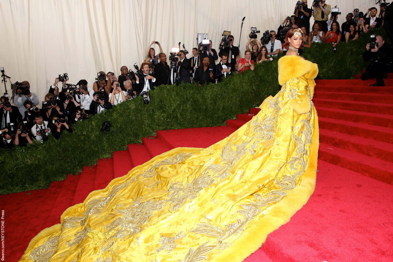 Rihanna made a very large, yellow statement on the carpet, wearing one of her most eccentric looks yet. She showed upsportinga massive golden GuoPei gown thatneededthree people to help her carryitup the steps. Trimmed with fur that wrapped around her shoulders like a shawl, the embellished gown had everyone talking.