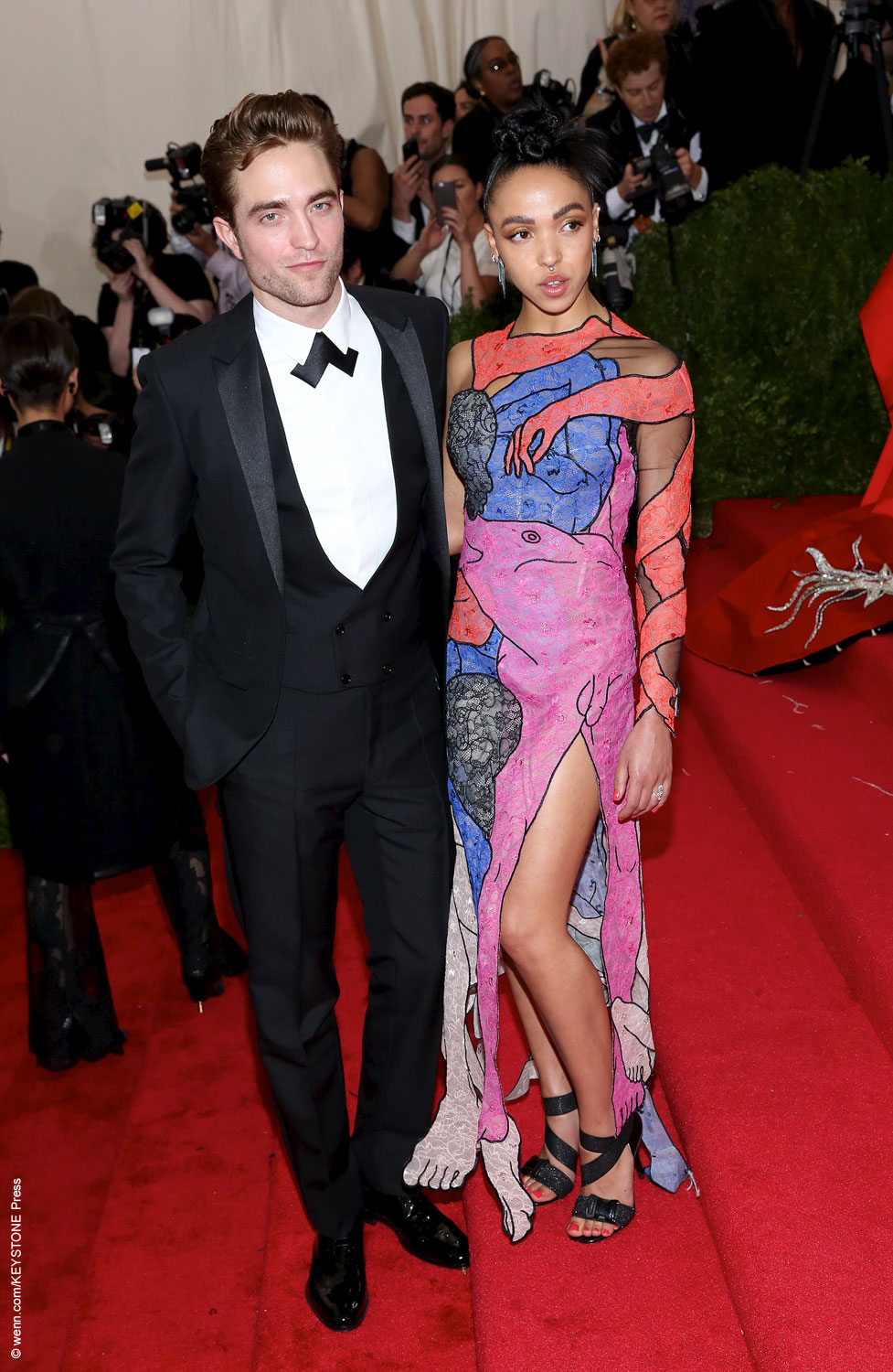 Robert Pattinson and his fiancée FKA Twigs walked the Met's red carpet together, their red carpet debut as a couple. Twigs got everyone talking when she wore a Christopher Kane dress printed with erotic body parts on it, while Robert looked handsome in a black tux.