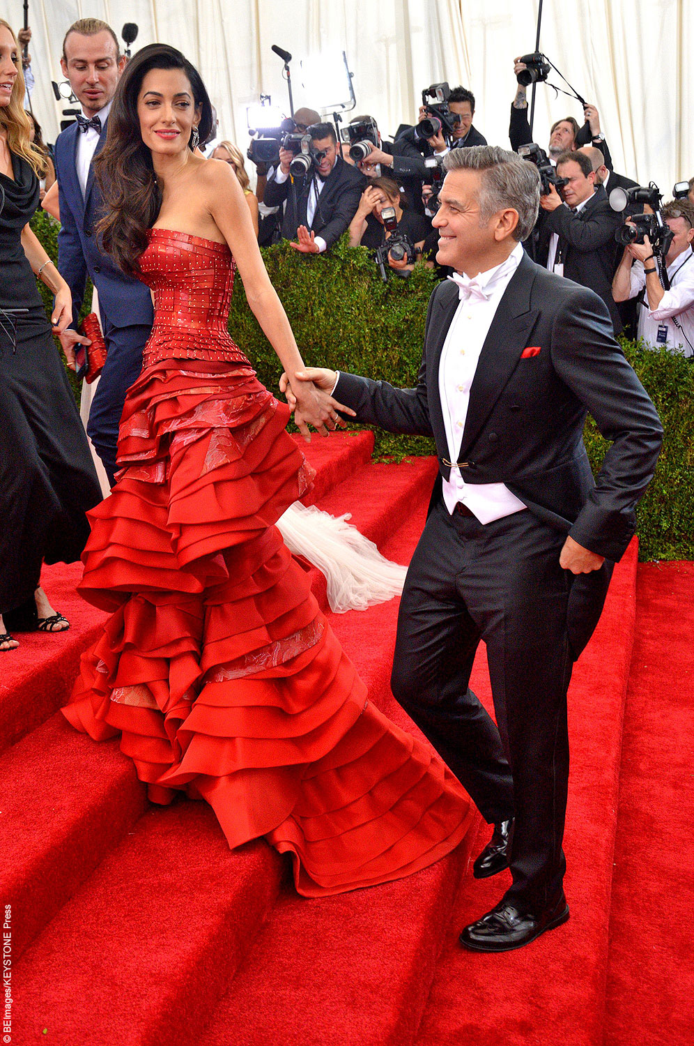 George Clooney and his wife Amal were all smiles when they hit the red carpet together. The happy couple looked beautiful together — Amal classy in a red Mason Margiela gown while George was dapper in his tux.
