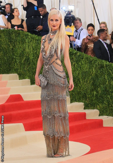 Model-actress Cara Delevingne's older sister Poppy didn't disappoint in this plunging silver tiered semi-sheer Marchesa floor-length gown that oozes vintage Hollywood glamour but also salutes the future. She topped off the figure-hugging, jewel-dripping dress with diamond chandelier earrings, a chunky choker and an Oroton clutch.
