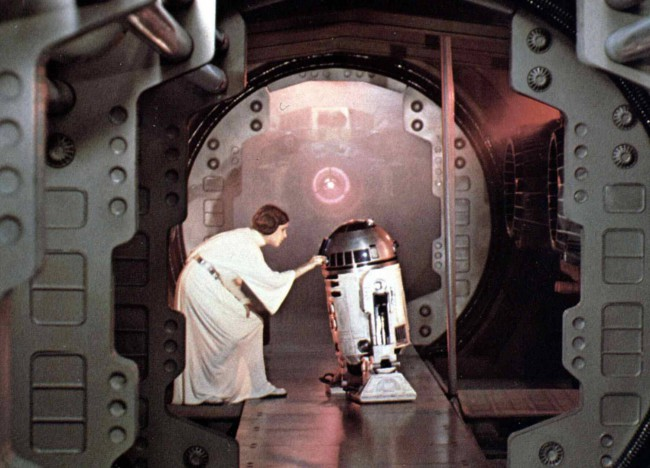 In one of Carrie's first lines in the first Star Wars movie (later titled A New Hope), as Princess Leia, she hid a secret message in beloved droid R2-D2. The message was for Jedi master Obi-Wan Kenobi (played by Alec Guinness), asking for help with her rebellion against the Empire.