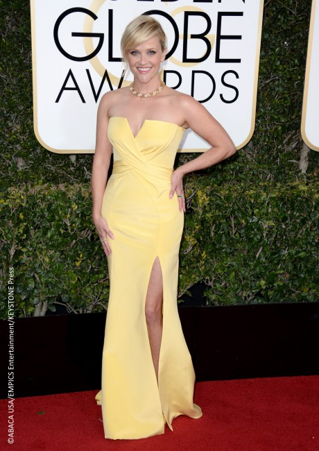 "Reese Witherspoon chose to go for, as she calls it, a ""classic Hollywood"" look as she walked the red carpet in a custom Atelier Versace cream yellow gown that displayed a high slit and a low-cut neckline. She neatly pinned her hair back and accessorized with Tiffany & Co. jewelry."