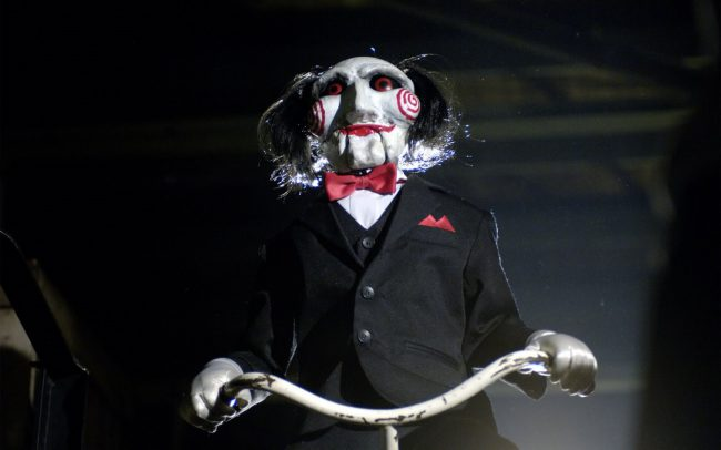 While Saw's (2004) tricycle-riding doll is not necessarily the evil being doing harm in the movie, its personification of the sadistic psycho, Jigsaw, makes it one and the same. Indeed, it's the first thing people remember when they think of the terrifying film franchise — if they're not imagining all the horrific and cringe-inducing ways […]