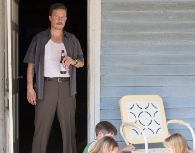 Will Chase, who plays Bob Nash, stands on his front porch. You can see the blue house from this image.
