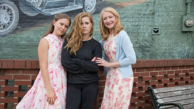 The mini-series' three leading ladies — Eliza Scanlen, Amy Adams and Patricia Clarkson — pose against a mural in Town Square.