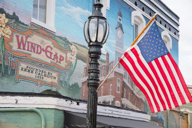 This is a close-up of the painting that reads: Wind Gap, founded by Zeke Calhoun, 1858. The actual mural reads: Barnesville, founded by Gideon Barnes, 1826.