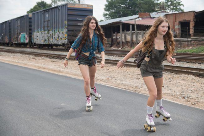 Amma's (Eliza Scanlen) close friends Kelsey (Violet Brinson) and Jodes (April Brinson) are seen skating beside the tracks.