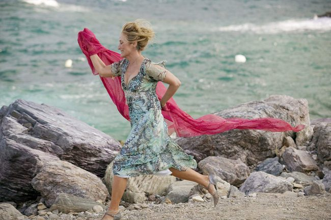 Meryl Streep runs along the rocks during a musical number at the bottom of the church.