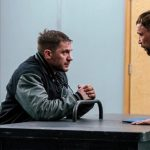 Eddie Brock (Tom Hardy) being interrogated by the police.