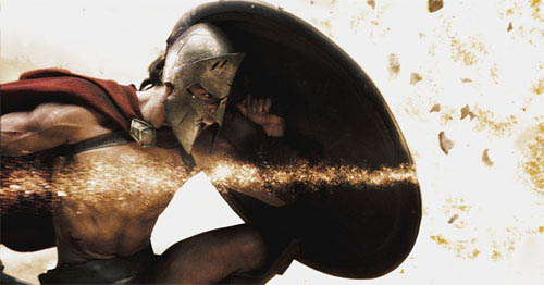 """Stelios (MICHAEL FASSBENDER) crouches behind his shield as shrapnel tears through the air in Warner Bros. Pictures', Legendary Pictures' and Virtual Studios' action drama """"300,"""" distributed by Warner Bros. Pictures.  - Large"""