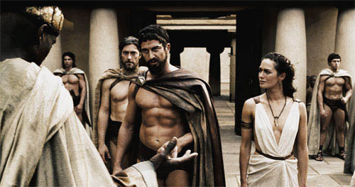 """Leonidas (GERARD BUTLER, center) warns the Persian Messenger (PETER MENSAH) to choose his words wisely as Captain (VINCENT REGAN, left) and Gorgo (LENA HEADEY) look on in Warner Bros. Pictures', Legendary Pictures' and Virtual Studios' action drama """"300,"""" distributed by Warner Bros. Pictures.   - Large"""