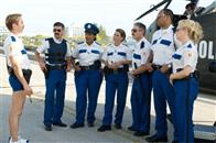 In Miami, Lt. Dangle (Thomas Lennon, left) reviews some strategy with his team: Travis Junior (Robert Ben Garant), Raineesha Williams (Niecy Nash), Cherisha Kimball (Mary Birdsong), James Garcia (Carlos Alazraqui), S. Jones (Cedric Yarbrough), Clementine Johnson (Wendi McLendon-Covey), and in the helicopter Deputy Trudy Wiegel (Kerri Kenney-Silver).