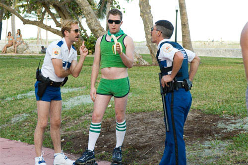 "In Miami, Lt. Jim Dangle (Thomas Lennon, left) and Dep. Travis Junior (Robert Ben Garant) encounter an old ""friend"" from Reno: Terry (Nick Swardson). - Large"