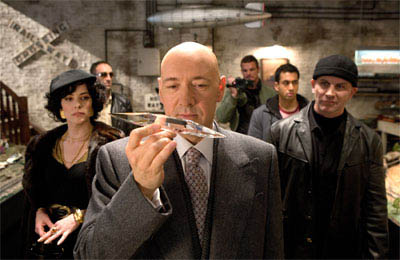 Lex Luthor (KEVIN SPACEY, center) examines one of Superman's crystals in the company of his partners in crime, (left to right) Kitty Kowalski (PARKER POSEY), Grant (VINCENT STONE), Riley (IAN ROBERTS), Stanford (KAL PENN) and Brutus (DAVID FABRIZIO) in a scene from Warner Bros. Pictures' and Legendary Pictures' action adventure Superman Returns.