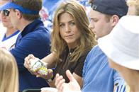 "Art dealer Brooke Meyers (JENNIFER ANISTON) passes a hot dog at the baseball game to the obnoxious heckler in the romantic comedy ""The Break-Up""."
