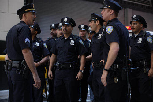 In <i>World Trade Center</i>,  Academy Award®-winning director Oliver Stone tells the true story of the heroic survival and rescue of two Port Authority policemen - John McLoughlin (Nicolas Cage, left) and Will Jimeno (Michael Peña, center) - who were trapped in the rubble of the World Trade Center on September 11, 2001, after they went in to help people escape.  Other officers serving with them - including Antonio Rodrigues (Armando Riesco, 2nd from right) joined them as they entered the buildings. - Large