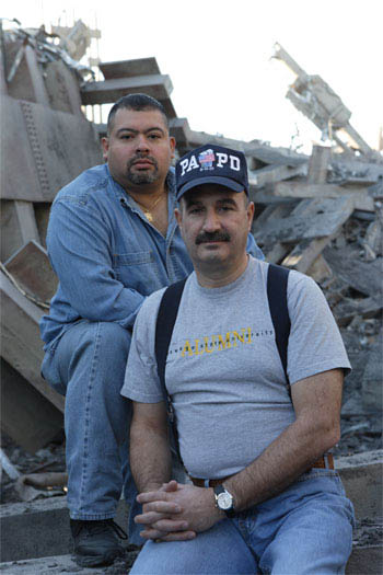 In <i>World Trade Center</i>,  Academy Award®-winning director Oliver Stone tells the true story of the heroic survival and rescue of two Port Authority policemen - John McLoughlin (right) and Will Jimeno (center left) - who were trapped in the rubble of the World Trade Center on September 11, 2001, after they went in to help people escape.  The officers are portrayed in the film by Nicolas Cage (center right) and Michael Peña (left), respectively. - Large